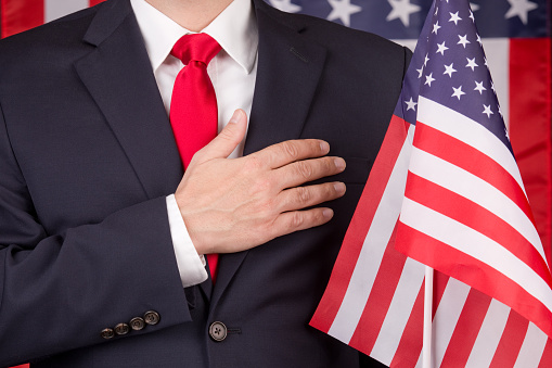 A man in a suit and red tie standing in front of an American flag with his right hand over his heart.